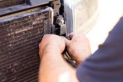 Dismantling broken car radiator to fix problem. Manual worker dismantling a car to pieces to fix the problem at a broken radiator in service Stock Image