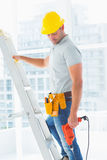 Manual worker with drill machine climbing ladder Royalty Free Stock Image