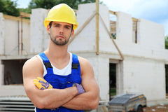 Manual worker in front of construction site. Attractive manual worker in front of construction site stock images