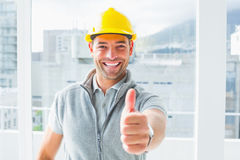 Manual worker gesturing thumbs up in building Royalty Free Stock Image