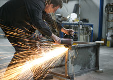 Manual worker grinding steel table Stock Photo
