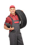 Manual worker holding a clipboard and a tire Stock Photography
