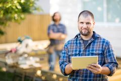 Manual Worker Holding Digital Tablet With Coworker. Portrait of mid adult manual worker holding digital tablet with coworker standing in background at Royalty Free Stock Images