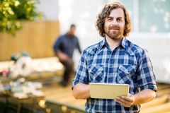 Manual Worker Holding Digital Tablet With Coworker. Portrait of mid adult manual worker holding digital tablet with coworker working in background at Stock Image