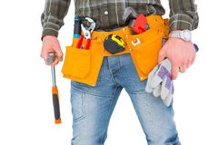 Manual worker holding gloves and hammer. Manual worker wearing tool belt while holding gloves and hammer on white background Stock Photos