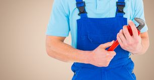 Manual worker holding a monkey wrench against beige background Royalty Free Stock Photography