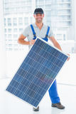 Manual worker holding solar panel in bright office. Full length portrait of manual worker holding solar panel in bright office stock photos