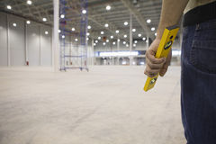 Manual Worker Holding Spirit Level In Warehouse Royalty Free Stock Photography