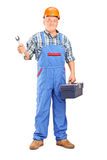 Manual worker holding a wrench. Full length portrait of a manual worker holding a wrench and tool box  against white background Royalty Free Stock Photography