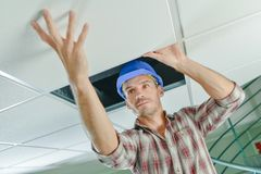 Manual worker inspecting ceiling. Against Stock Photos