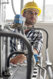 Manual worker looking away while examining machine in industry Stock Images