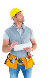 Manual worker looking away while writing on clipboard. Manual worker looking up while writing on clipboard over white background royalty free stock photography