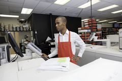 Manual worker looking at cash register machine stock photo