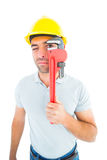 Manual worker looking through monkey wrench Stock Photos