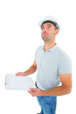 Manual worker looking up while holding clipboard Stock Photos