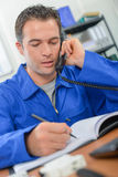 Manual worker making call in office Stock Image
