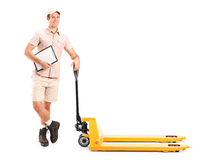 Manual worker next to a fork pallet truck. Full length portrait of a manual worker holding a clipboard and fork pallet truck  on white background Stock Photos