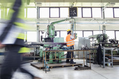 Manual worker operating machinery at metal industry stock photography