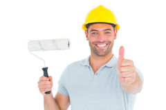 Manual worker with paint roller gesturing thumbs up Stock Photos
