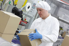 Manual worker at production line dealing with boxe. Manual worker in white uniform,cap and blue gloves, at production line dealing with boxes royalty free stock photo