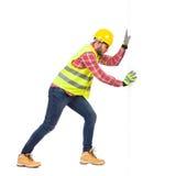 Manual worker pushing white wall Stock Image