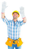 Manual worker raising hands while looking up. Smiling manual worker raising hands while looking up on white background royalty free stock photo