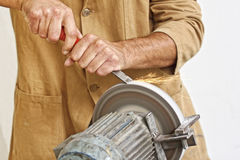 Manual worker sharp his tool Stock Images