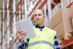 Manual worker with tablet pc at warehouse Royalty Free Stock Photo