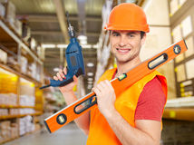 Manual worker with tools at warehouse. Portrait of smiling manual worker with tools at warehouse Stock Photo