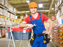 Manual worker with tools at warehouse. Portrait of smiling manual worker with tools at warehouse royalty free stock photo