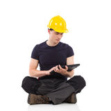 Manual worker using a digital tablet. Portrait of manual worker using digital tablet and sitting on a floor with legs crossed. Full length studio shot isolated Stock Photos