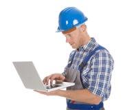 Manual worker using laptop Royalty Free Stock Image