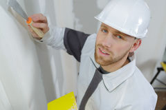 Manual worker with wall plastering tools inside house Stock Photography