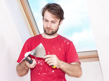 Manual worker with wall plastering tools inside a house Royalty Free Stock Images