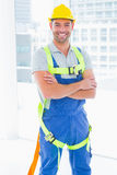Manual worker wearing safety harness in bright office. Portrait of happy manual worker wearing safety harness standing arms crossed in bright office stock image
