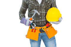 Manual worker wearing tool belt while holding hammer and helmet Stock Photos