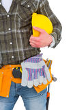 Manual worker wearing tool belt while holding helmet Stock Images