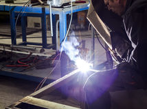 Manual worker welding metal table Stock Photography