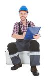 Manual worker writing on clipboard over white background. Full length portrait of confident manual worker writing on clipboard while sitting on trunk over white Stock Images