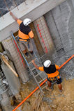 Manual workers inspecting a concert wall in construction site Stock Photos