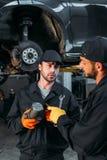 Manual workers repairing car with tools. In mechanic workshop stock image