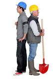 Manual workers standing back to back Royalty Free Stock Photo