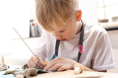 Manual workshops for children, clay molding. The boy is clawing out of clay at a plastic workshop Royalty Free Stock Images