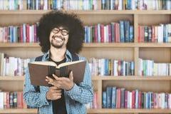 Manuale della tenuta dello studente di afro in biblioteca Immagine Stock