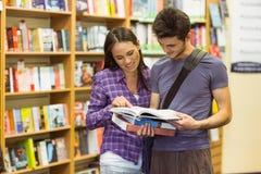 Manuale sorridente della lettura dello studente degli amici Fotografia Stock Libera da Diritti