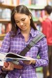 Manuale sorridente della lettura dello studente universitario Fotografie Stock Libere da Diritti
