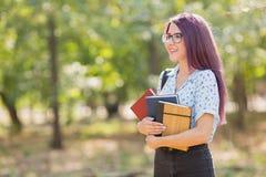 Manuali della tenuta dello studente su uno sfondo naturale Ragazza con i libri Apprendimento del concetto Copi lo spazio Fotografia Stock