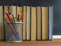 Manuali e rifornimenti di scuola su una tavola, contro un fondo della lavagna con gesso Concetto della scuola con il copyspase Immagini Stock