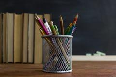Manuali e rifornimenti di scuola su una tavola, contro un fondo della lavagna con gesso Concetto della scuola con il copyspase Fotografie Stock Libere da Diritti