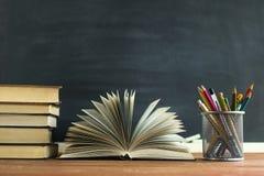 Manuali e rifornimenti di scuola su una tavola, contro un fondo della lavagna con gesso Concetto della scuola con il copyspase Immagini Stock Libere da Diritti